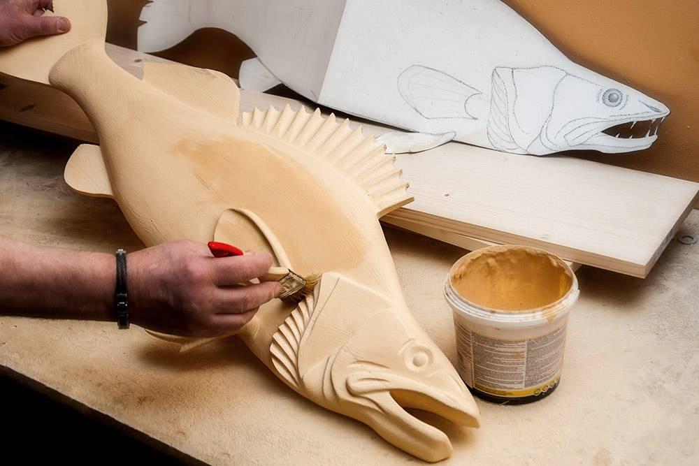 Мастер сравнивает готовую рыбу с лекалом и покрывает скульптуру грунтовкой, чтобы краска лучше ложилась