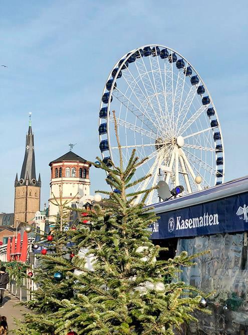 Вид на искривленную крышу базилики Святого Ламберта и башню Шлосстурм. Во время рождественских праздников неподалеку устанавливают несколько аттракционов и колесо обозрения. В 2018&nbsp;году билет на колесо стоил 7,5€ (550<span class=ruble>Р</span>)