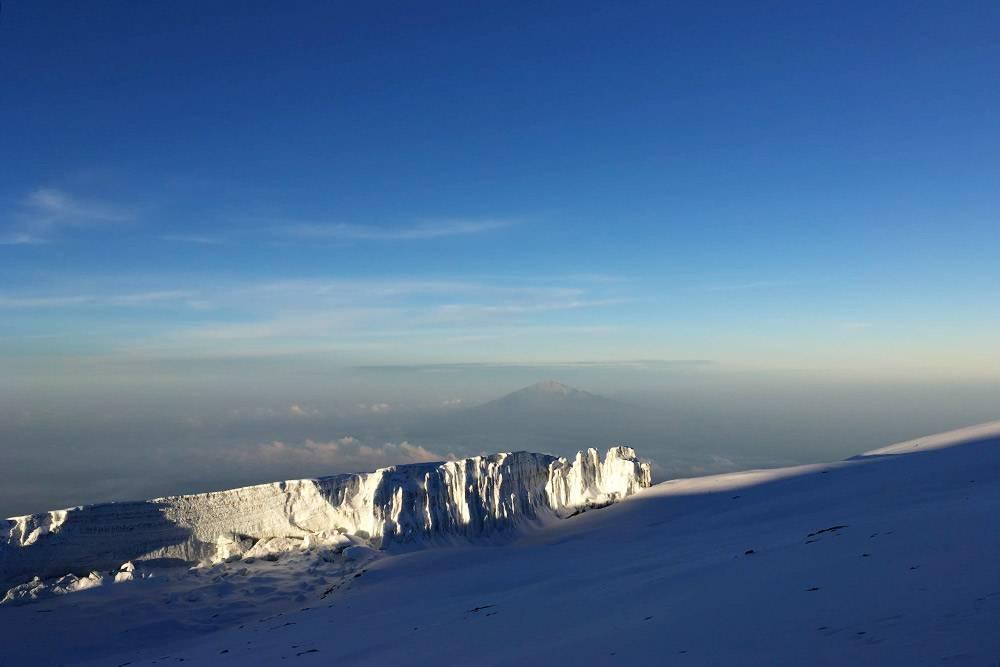 Вид с вершины Килиманджаро на ледники на склонах и пик Меру — вдалеке на заднем плане