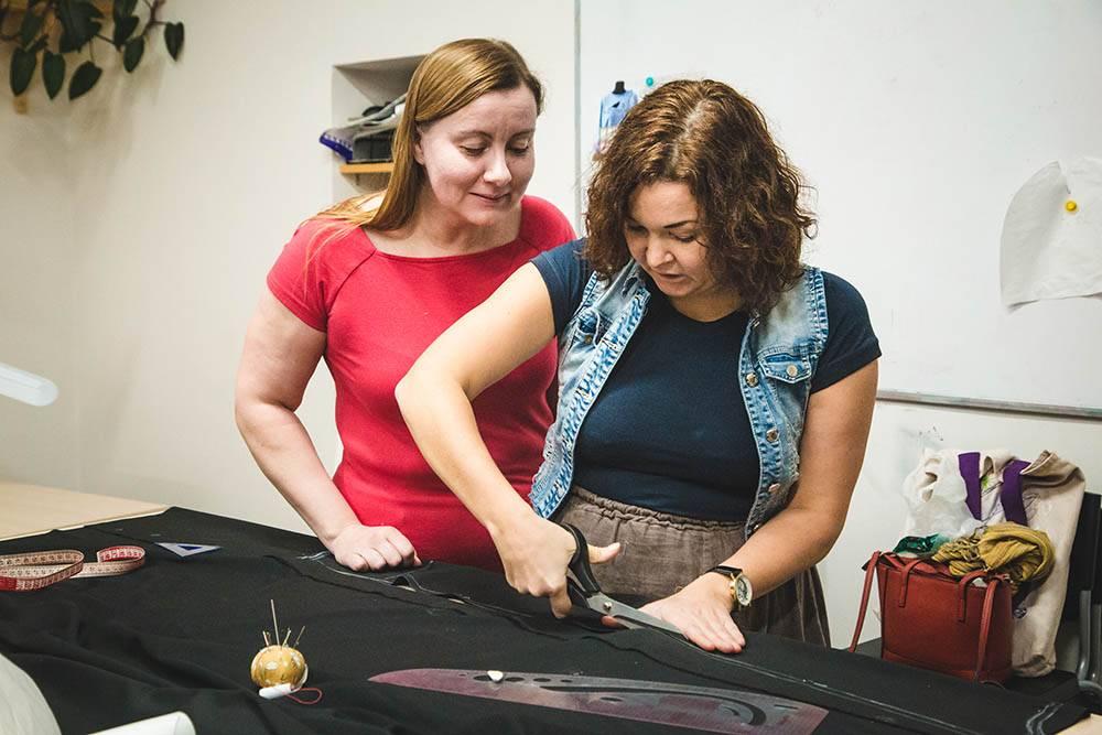 Преподаватель показывает ученице, как раскраивать ткань