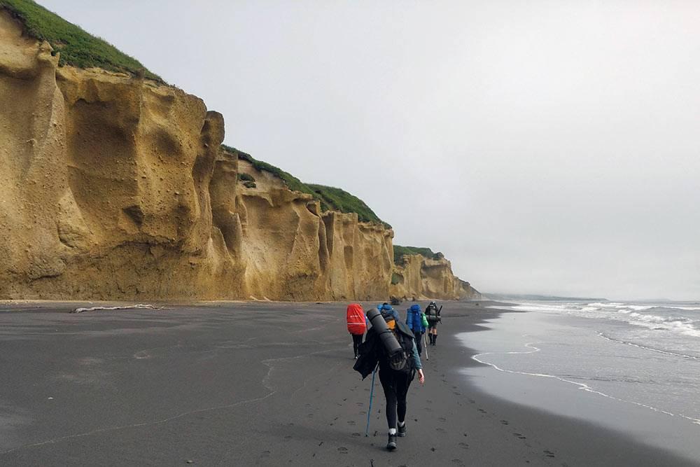 Желтые скалы напобережье Тихого океана вКроноцком заповеднике. Инспектор торопилнас, чтобы мыуспели пройти этоместо донаступления прилива, иначе пришлосьбы либо купаться вледяной воде, либокарабкаться вверх поотвесным скалам