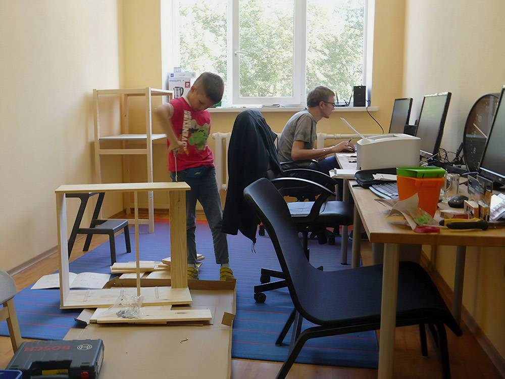Ремонт в офисе не делали. Поставили свою мебель и светильники. На фото мебель собирает сын Сергея — Никита