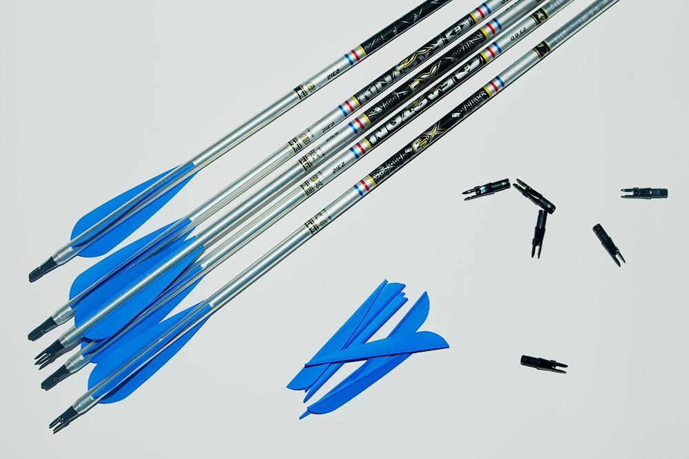 Слева на фото — хвост собранной стрелы. Справа — синие резиновые перья и черные хвостовики