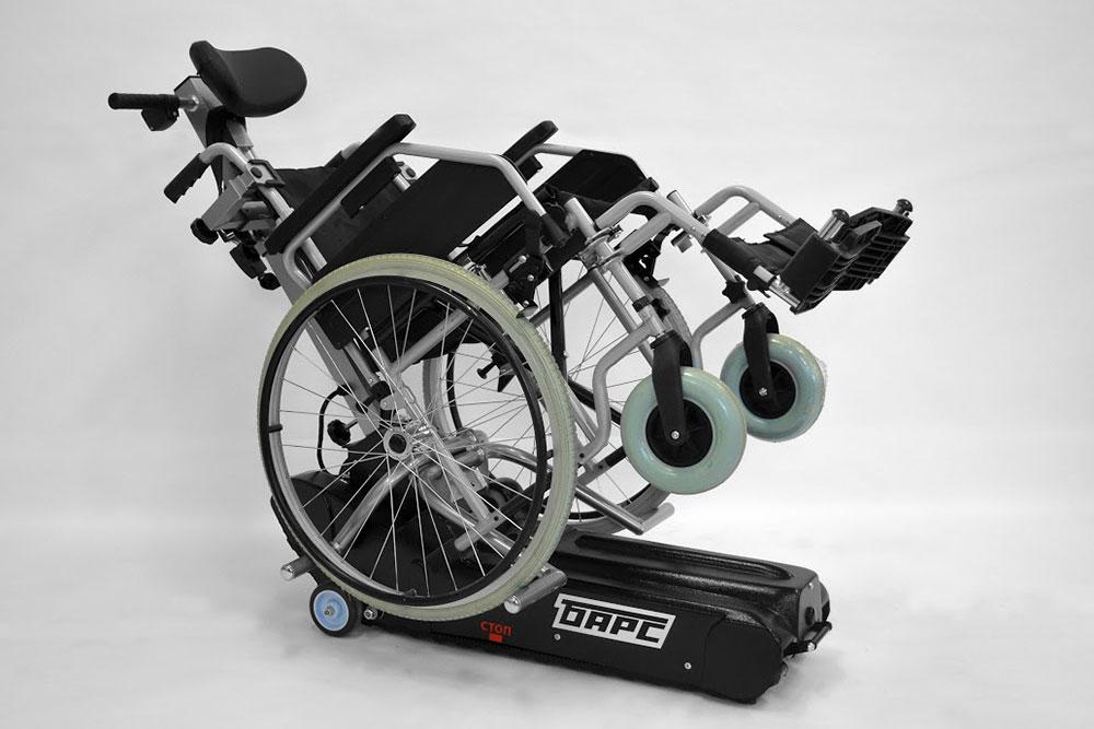 Инвалидная коляска вместе с человеком крепится к подъемнику, и он сам сползает или заползает по лестнице — человек только направляет. Ставит коляску в газель и спускает ее из газели тоже подъемник