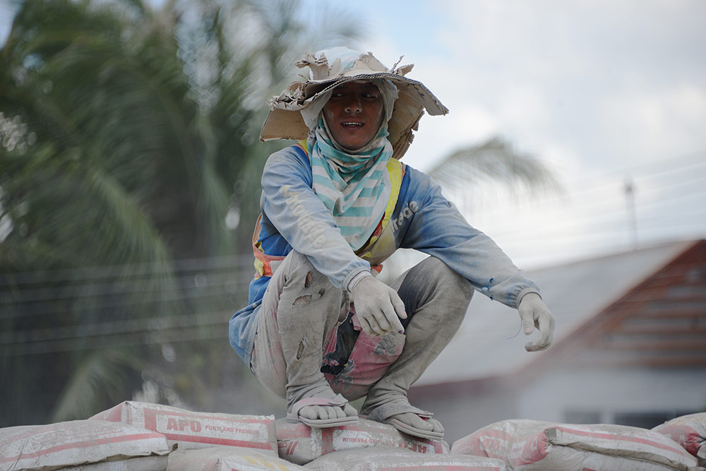 Грузчик на мешках цемента в городе Давао
