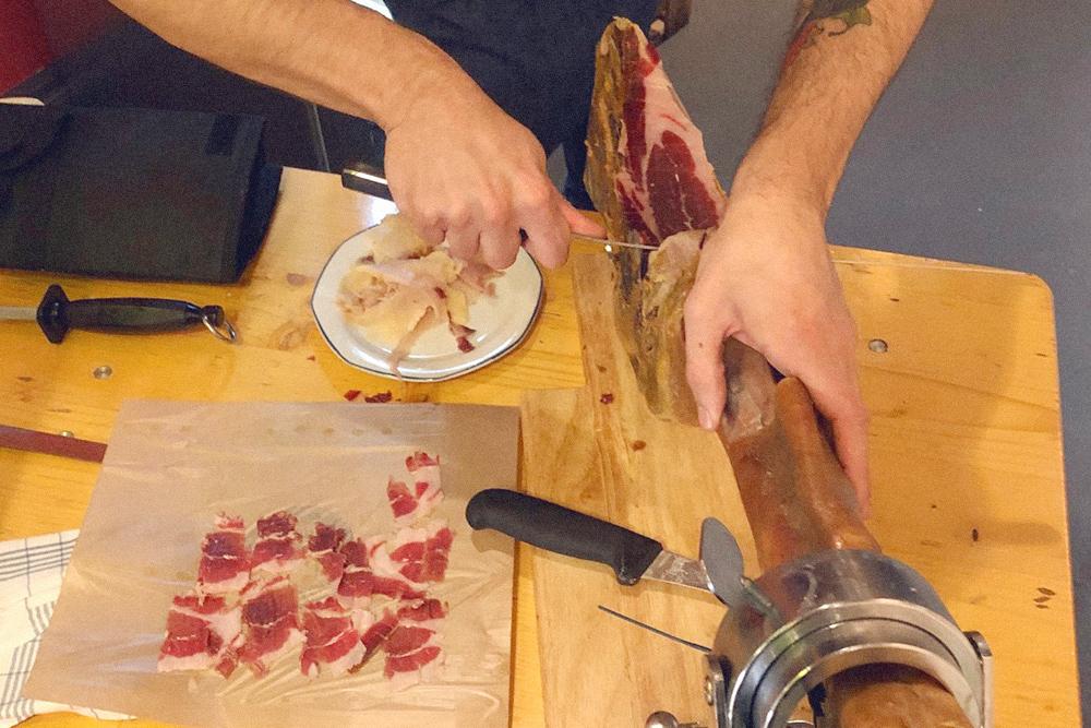 Мигель из гастролавки Vom Einfachen das Gute нарезает хамон специальным ножом. Так кусочки нарезаются вдоль волокон и получаются правильной толщины. 100г такого хамона стоят 5€. Бывает хамон и по 20€ за 100г