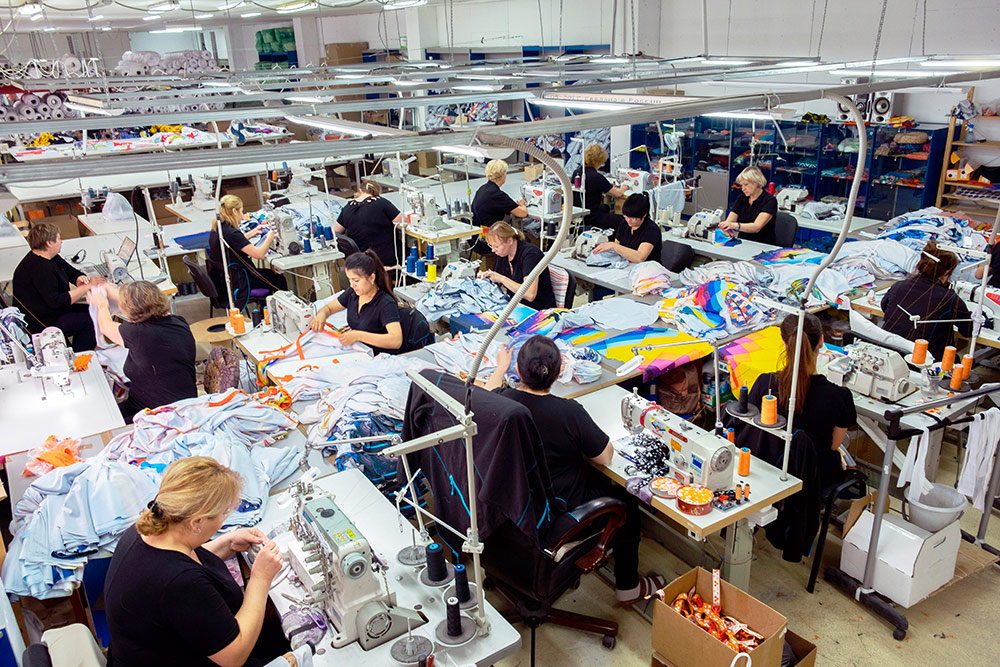 Рабочий цех: швеи за работой, за ними — раскройные столы, у дальней стены — стеллажи с сырьем
