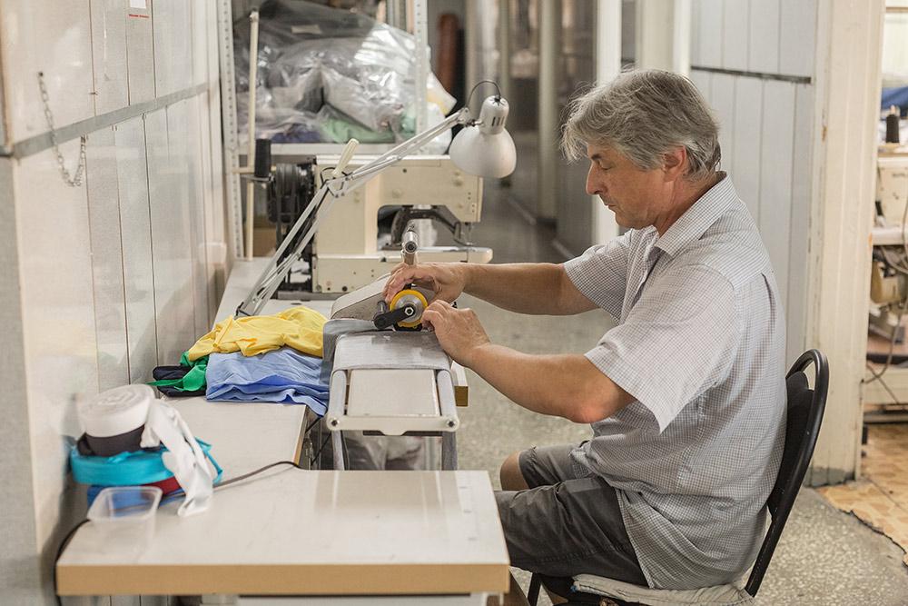 Разнорабочий — это самый универсальный сотрудник цеха. На фото он нарезает окантовку для обработки воротников на футболках