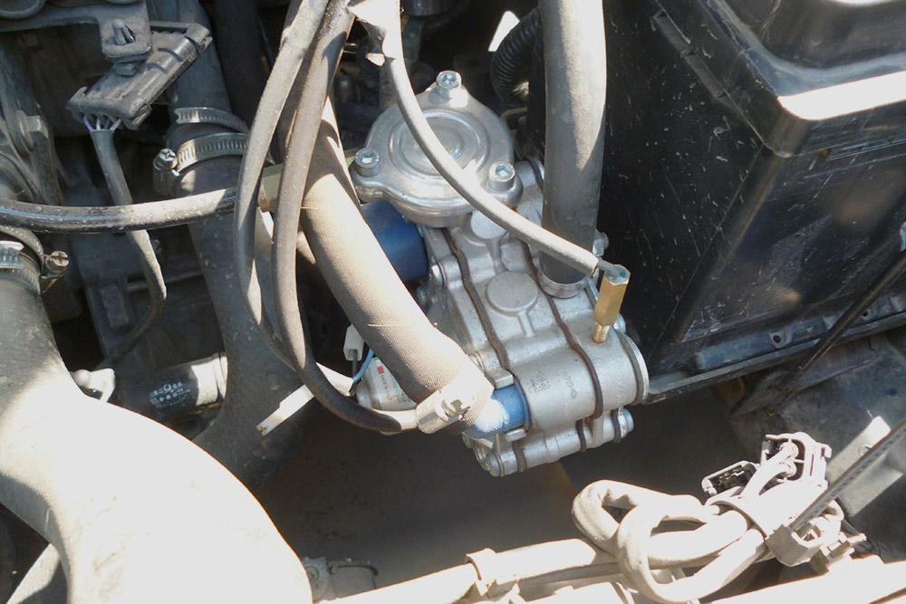 Это редуктор. В него газ попадает из баллона под собственным давлением. В редукторе давление газа снижается, а сам он подогревается охлаждающей жидкостью двигателя до 40°C