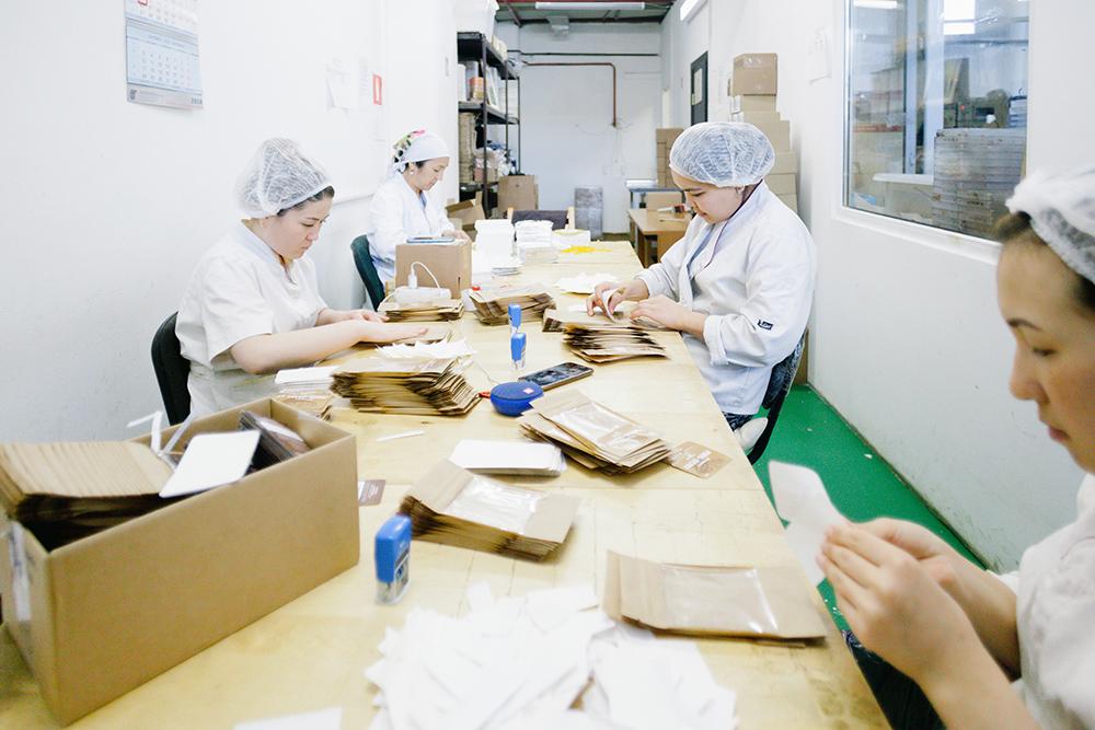 Упаковщицы за смену заворачивают в коробочки 500плиток шоколада