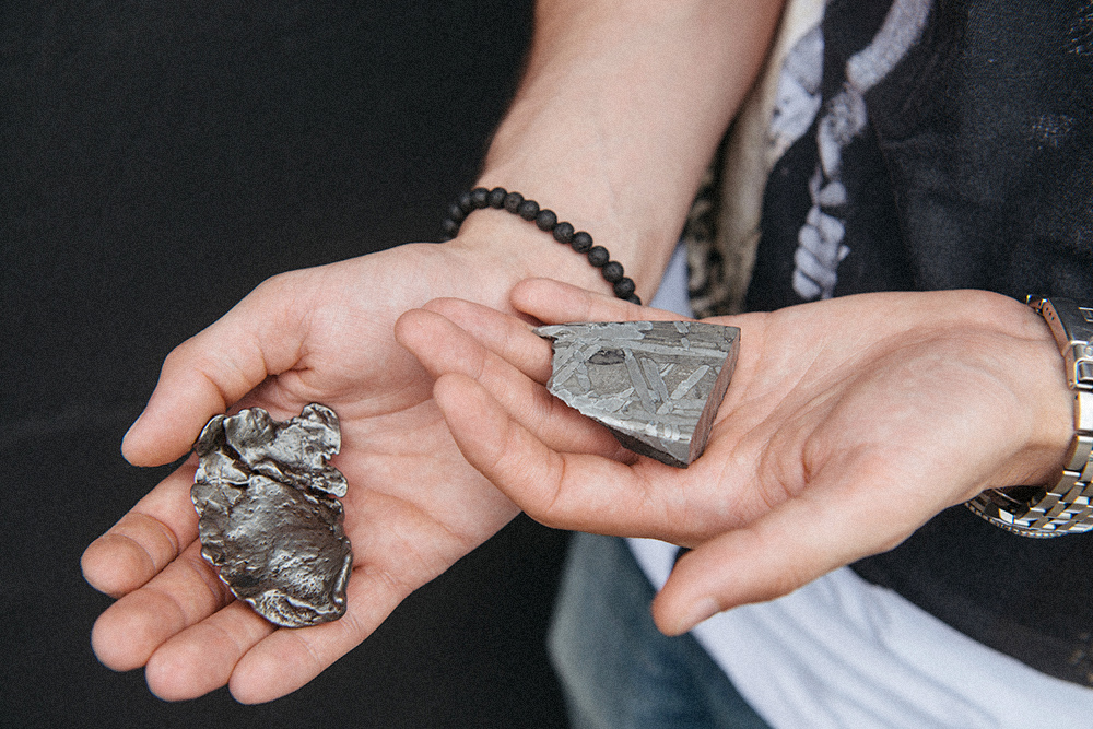 В левой руке — железокаменный метеорит Сеймчан, в правой — железный Сихотэ-Алинь
