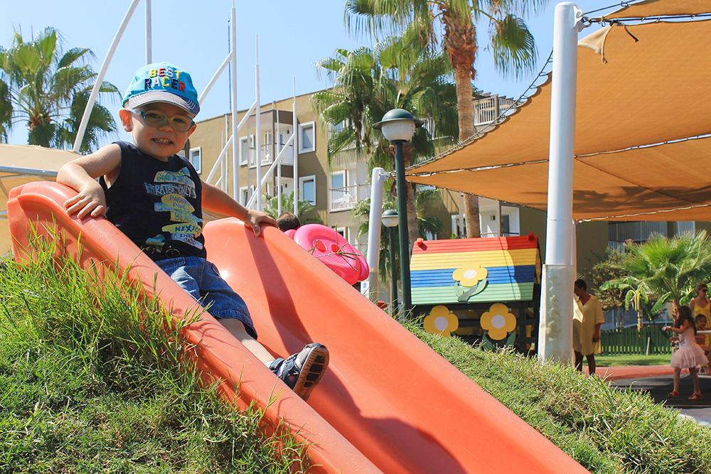 На улице для детей установлены горки, качели, веревочные лестницы и батуты
