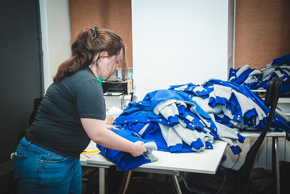 Толстовки отгладили и теперь упаковывают их перед отправкой в печатный цех