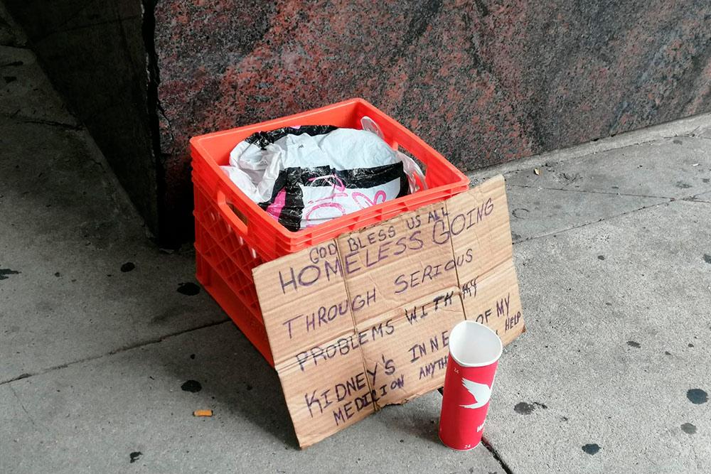 На табличке написано, что бездомный столкнулся с серьезными жизненными трудностями, а еще у него проблемы с почкой — просит денег на лечение