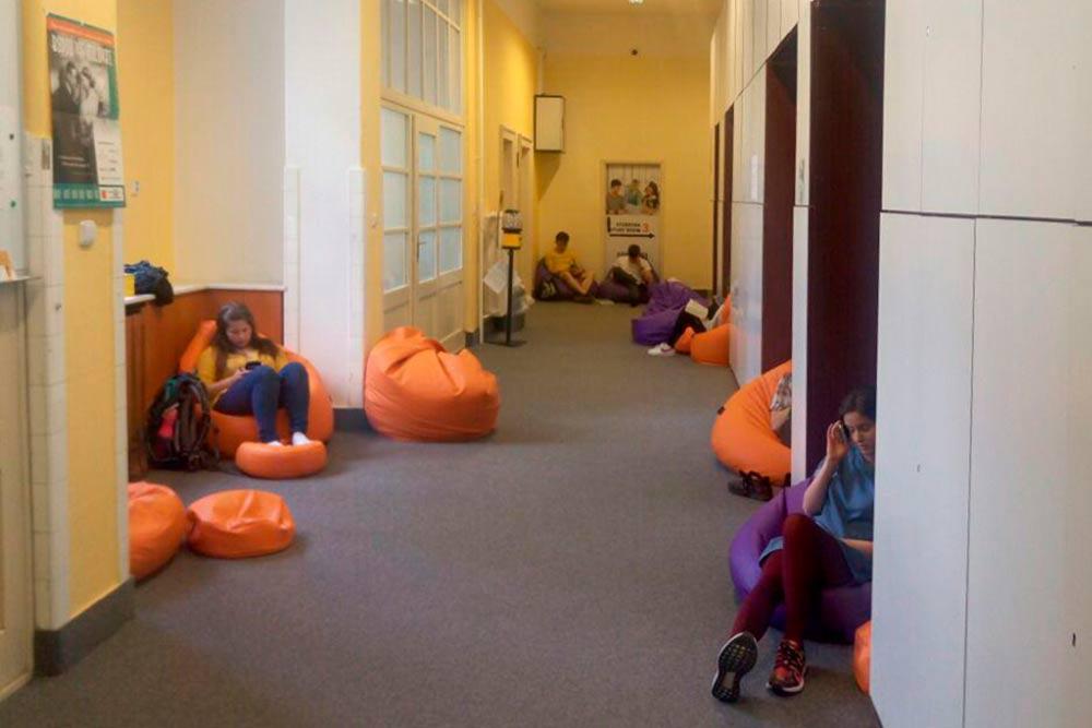 В коридоре учебных комнат студенты общаются, обедают и могут даже поспать в кресле-мешке