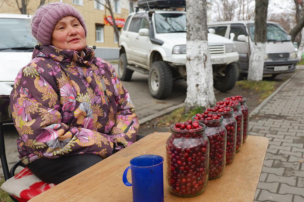 Корсаков. Бабушка продает клюкву, собранную «на болоте среди медведей», по 500 рублей за литр