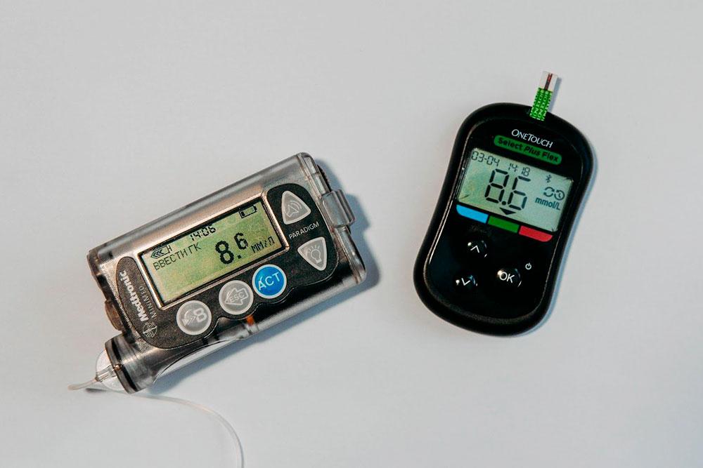 Уровень глюкозы в крови я измеряю глюкометром — на фото он справа. В верхний слот вставлена одноразовая тест-полоска. Помпа — на фото слева. Я ввожу в нее показатели глюкозы и сколько граммов углеводов собираюсь съесть. А она рассчитывает необходимую дозу инсулина