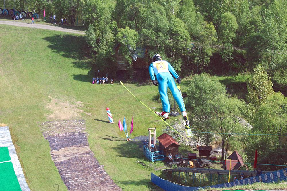 Соревнования по прыжкам на лыжах с трамплина проводят и летом: спортсмены приземляются на специальное покрытие из пластиковых щеток