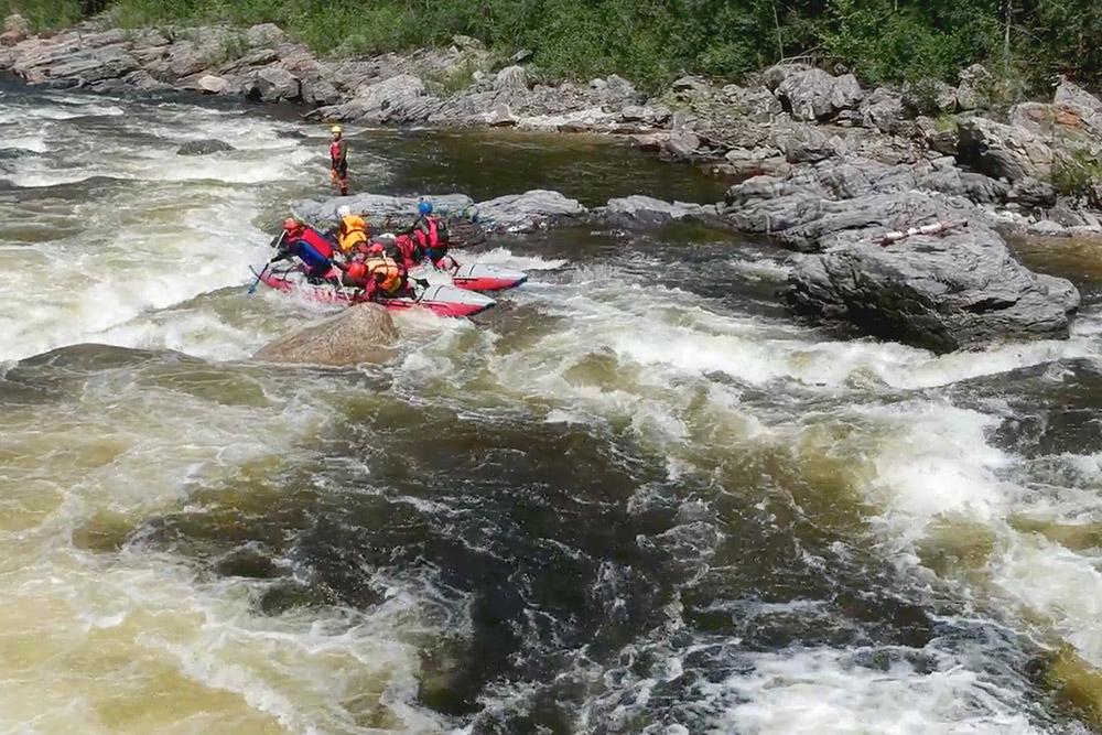 Катамаран нашей команды проходит вторую ступень порога Мунгул-Гольский 5 категории сложности на реке Снежной. Поодаль на камне стоит руководитель похода со спасательной выброской — на случай, если кто-то выпадет из катамарана