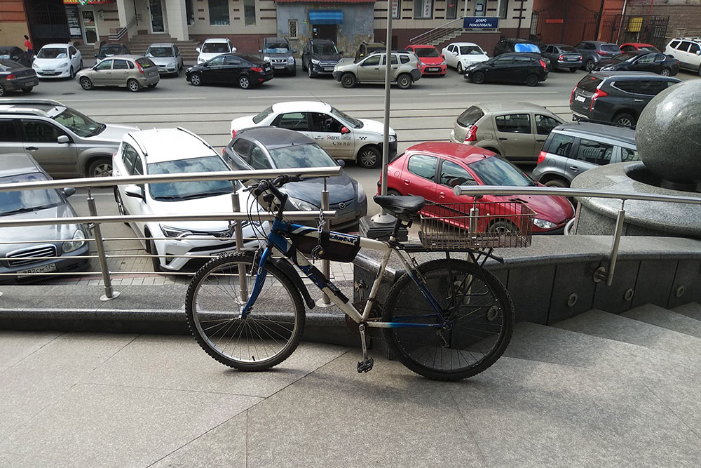 Кто-то припарковал велик прямо к перилам возле входа в большой офисный центр