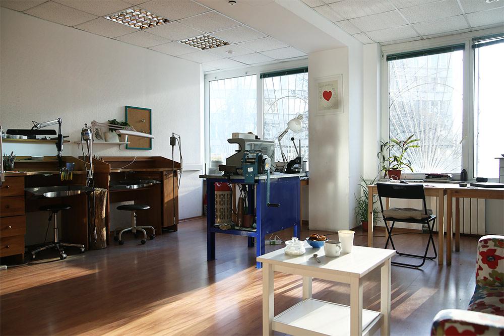 Мастерская на Звездном бульваре. Комната разделена на зоны: гостиная для посетителей, письменный стол, рабочие верстаки и тумбы с оборудованием