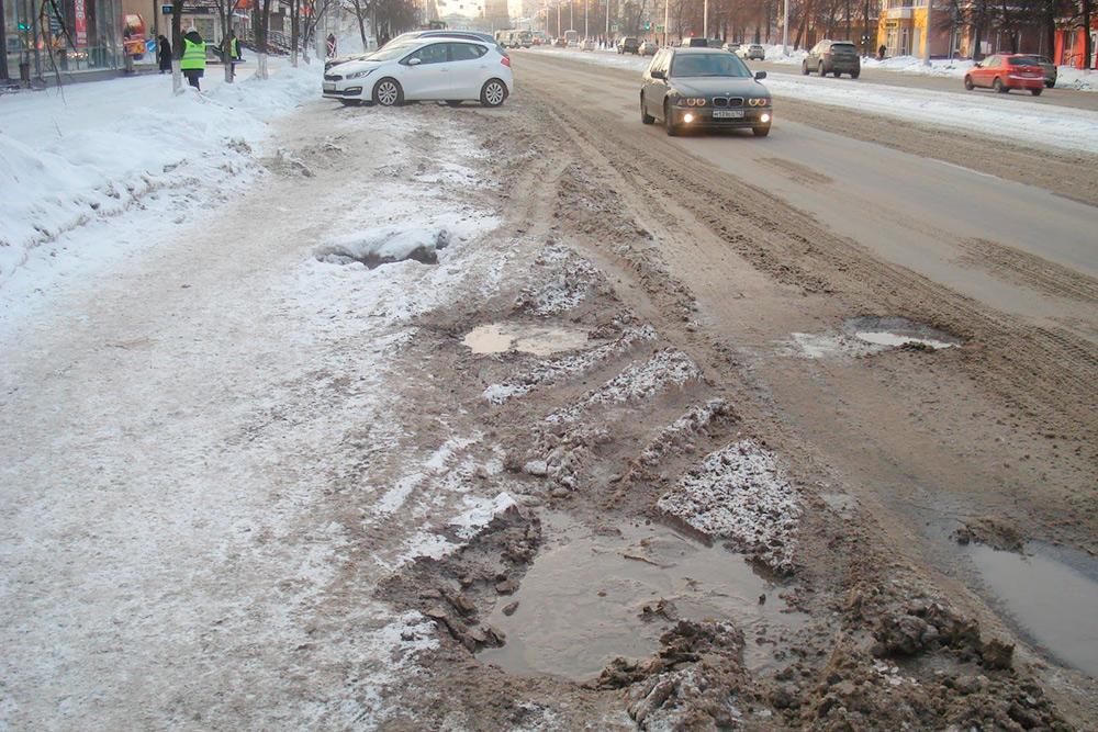 Это одна из основных магистралей Кемерова — проспект Ленина. Вдоль парковки оборудован небольшой тротуар, но зимой он завален снегом
