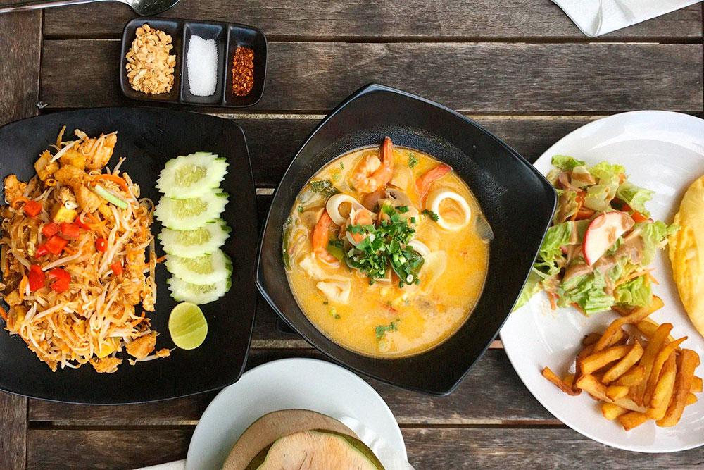 Слева — лапша пад тай с курицей, посередине — суп том-ям с креветками, справа — омлет с салатом, рядом стоит зеленый кокос