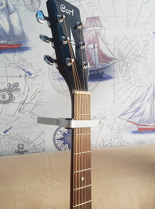 Каподастр для акустической гитары. Сейчас он установлен так, что все струны зажаты на втором ладу