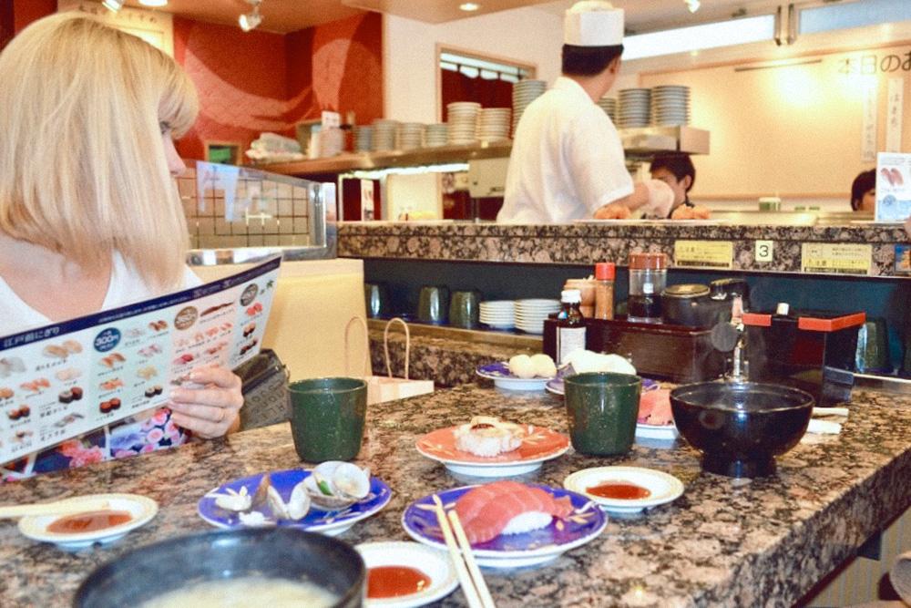 Это кайтен-суши, здесь готовые блюда движутся по конвейерной ленте. Ничего заказывать не нужно: взял, что нравится, и съел. Цена зависит от цвета тарелки