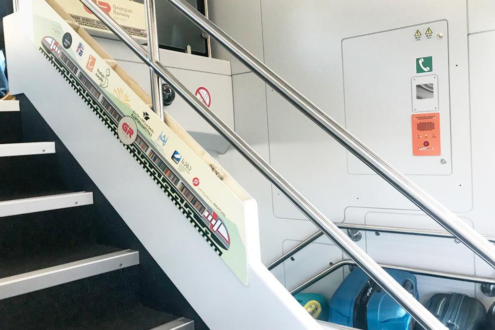 Книжная полка с изображением поезда в вагоне поезда Тбилиси — Батуми. Во время поездки там можно взять книгу или журнал и приятно провести время в путешествии