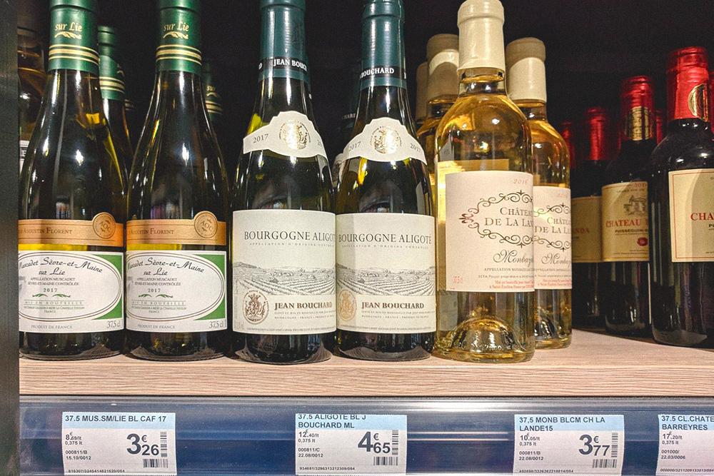 Неплохое вино в Париже стоит от 4€ (284 рубля) за бутылку. Выгоднее брать большой формат: 750 мл «Бургонь Алиготе» стоит 6,92€ (491рубль), а 375 мл — 4,65€ (330рублей)