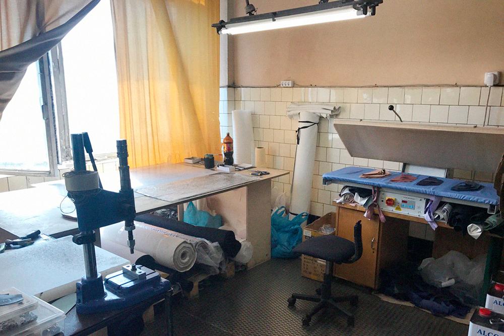Это уголок закройщика. Слева — маленький стол с пневмопрессом для установки фурнитуры и плитой под ручные пробойники, с их помощью делают отверстия под фурнитуру. В центре — раскройный стол, справа — термопресс длядублирования, внизу — 12-литровые банки с резиновым клеем
