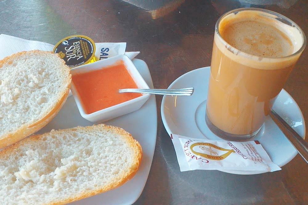 Типичный андалусский завтрак: кофе с молоком, поджаренный хлеб, оливковое масло и протертый томат
