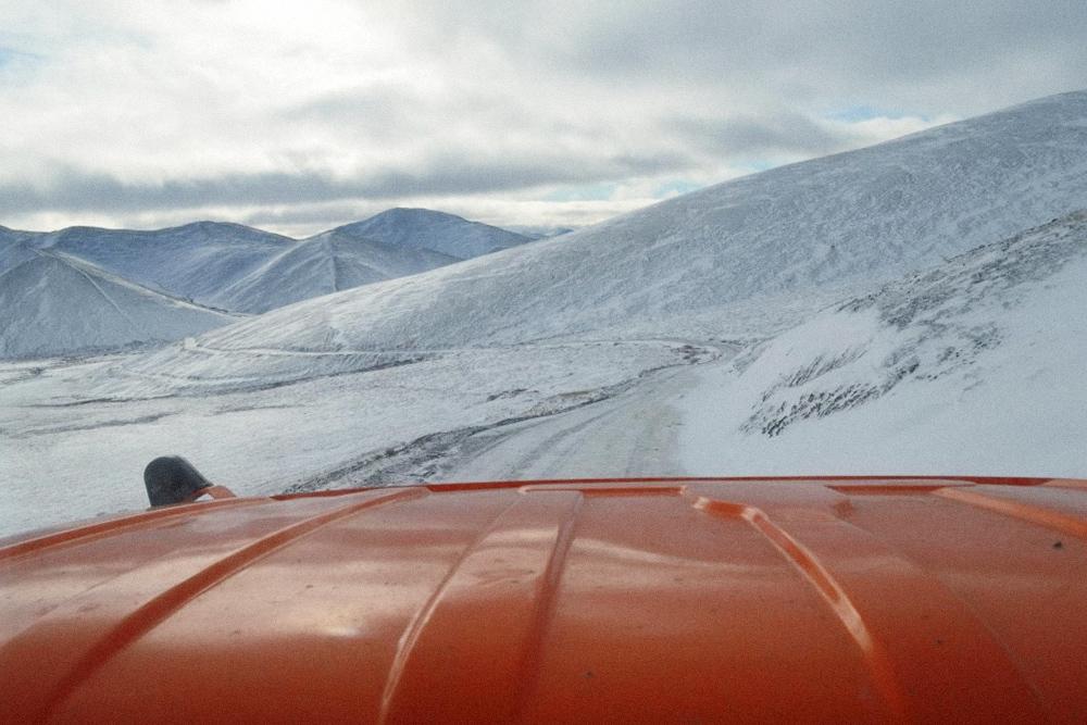 Зимняя дорога идет вдоль сопок к скалам Кекурам