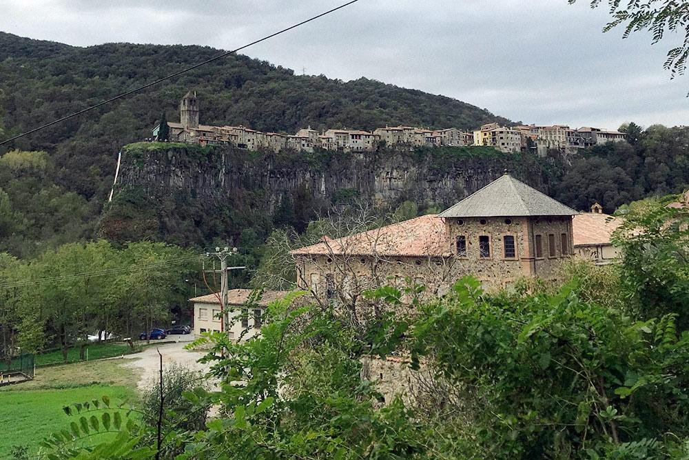 На заднем плане — Кастельфольит-де-ла-Рока. Город состоит из двух рядов домов, которые построены из вулканической породы