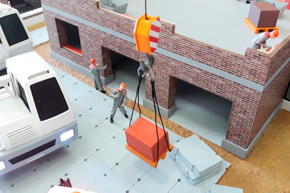 Молодые макетчики подготовили макет длястроительной компании. Техника движется: кран передает кирпич на второй этаж