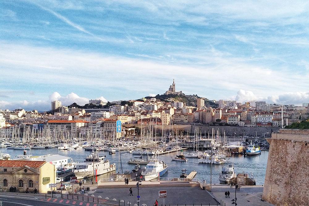 Вид на Старый порт Марселя. Сюда раньше приходили суда и здесь же велись все морские дела. Теперь в городе есть современный пассажирский и грузовой порт. На холме виднеется еще одна достопримечательность города — собор Нотр-Дам-де-ла-Гард