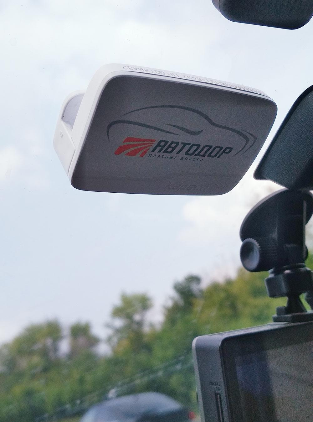 Так выглядит транспондер на лобовом стекле: белая коробочка с надписью «Автодор»