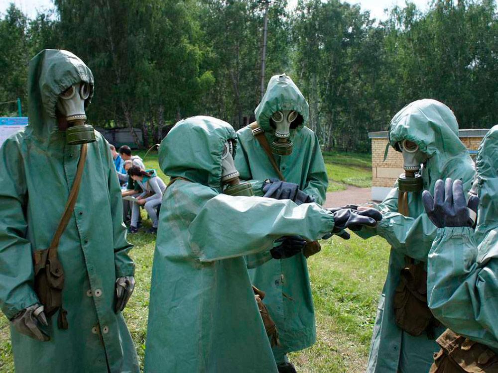 Занятие по радиационной, биологической и химической защите. Служащие тренируются быстро и правильно надевать общевойсковой защитный комплект — специальный костюм для защиты от заражения. На фото руководитель занятия проверяет, правильно ли военнослужащий надел костюм. Фото: «Мир космоса»