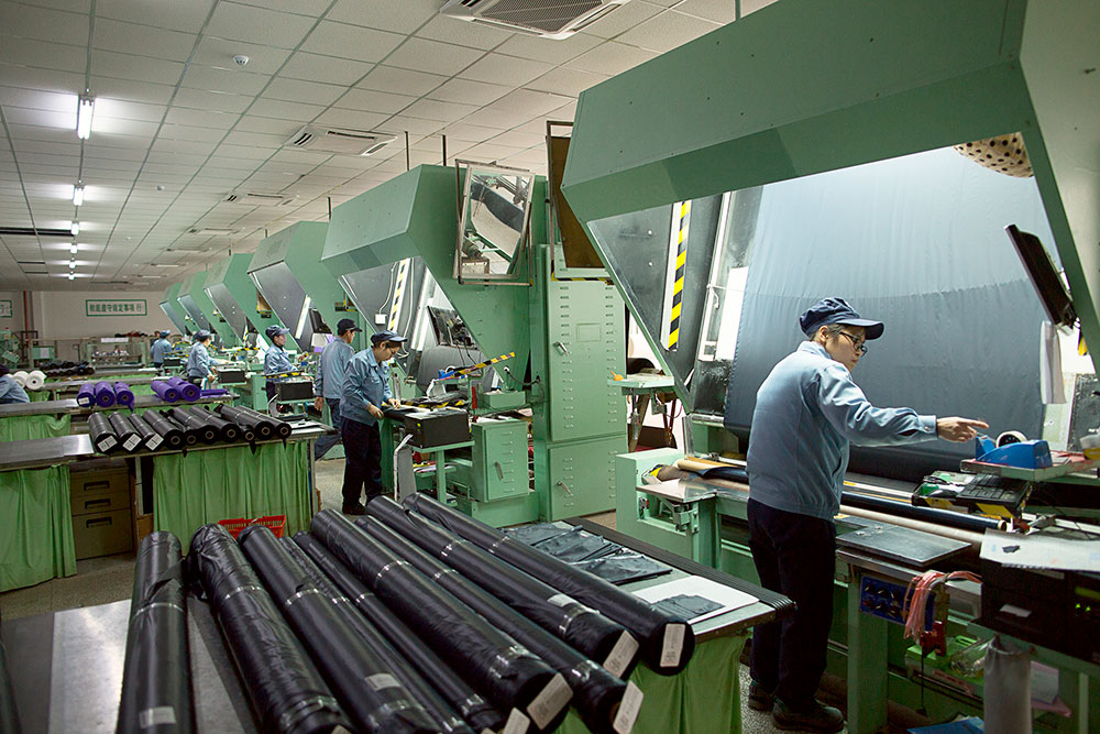 Работники ткацкой фабрики проверяют качество ткани и отмечают брак. Рулон ткани проматывают перед специальной лампой и смотрят на просвет. Готовые рулоны упаковывают в пластик, чтобы защитить от влажности и света