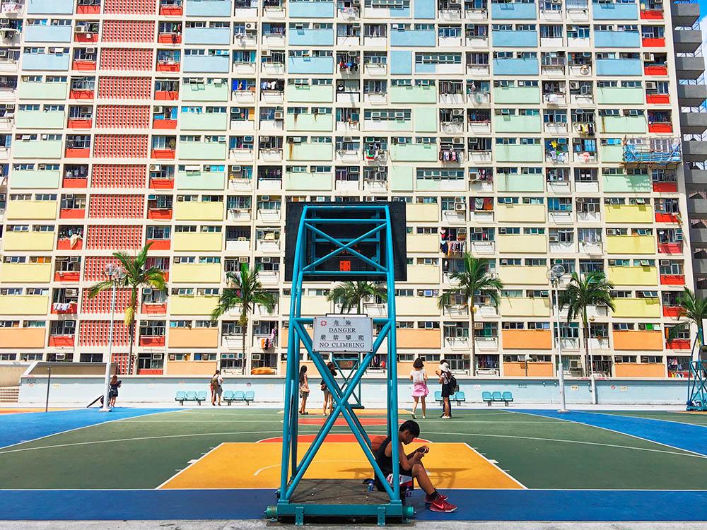 В Гонконге много фотогеничных зданий, но часто условия жизни в них не такие радужные. Название этого жилого комплекса переводится как «радужный дом». Эта баскетбольная площадка находится на крыше автостоянки, большинство людей приходит сюда сделать фотографии