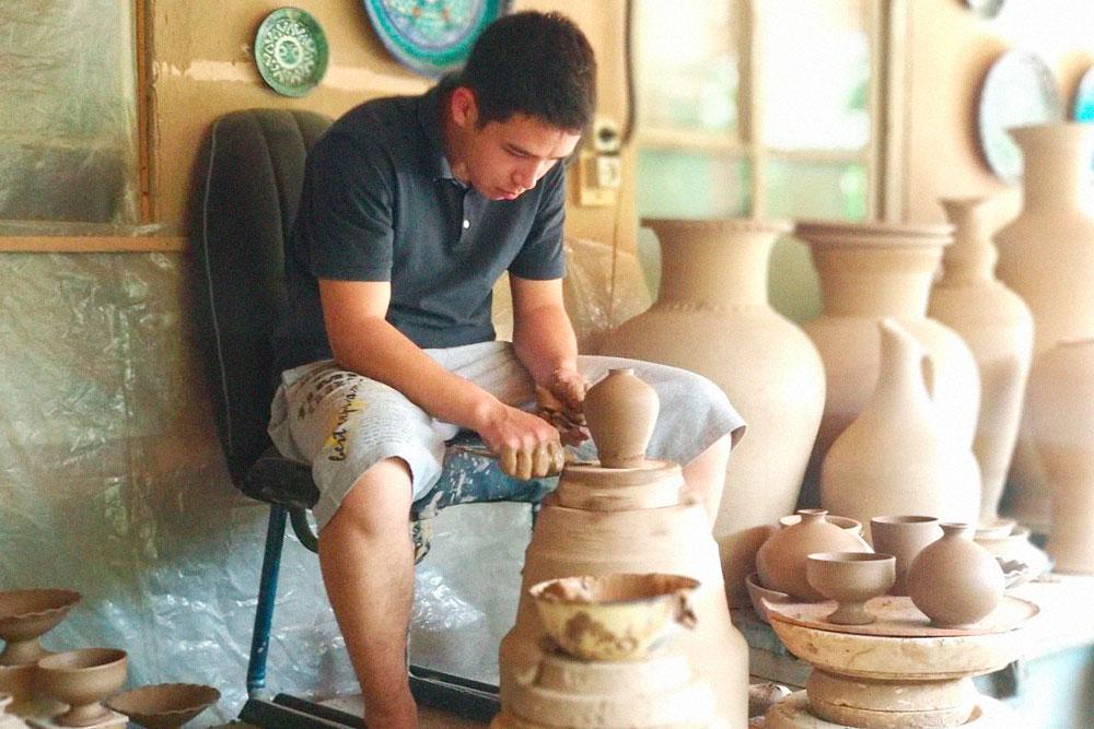 Ученик делает глиняные заготовки на гончарном круге