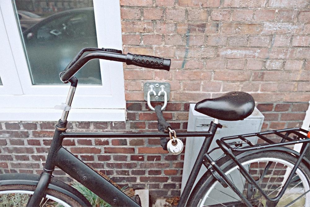 Так паркуют велосипеды в Амстердаме. Владелец прицепил велосипед к крюку в стене и заблокировал заднее колесо, чтобы нельзя было уехать. Два замка надежнее, чем один, но переднее колесо все еще могут украсть