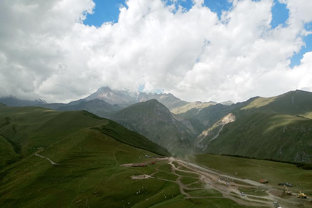 Вершина горы Казбек скрыта облаками. Здесь ветрено и прохладно: по ощущениям 16—18 °C. Советую брать теплую одежду