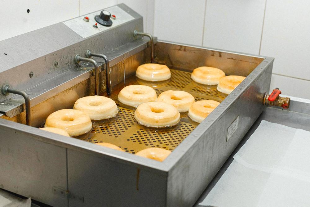 После обжариваем пончики во фритюре по три минуты с каждой стороны. Если медлить с обжаркой и не подогреть масло до 180°С — пончики сгорят или впитают слишком много масла
