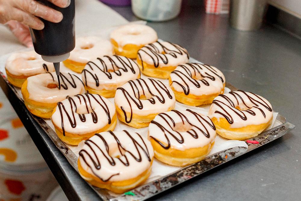 На последней станции пончики украшаем разноцветной глазурью с помощью диспенсеров длясоусов и кондитерской посыпкой