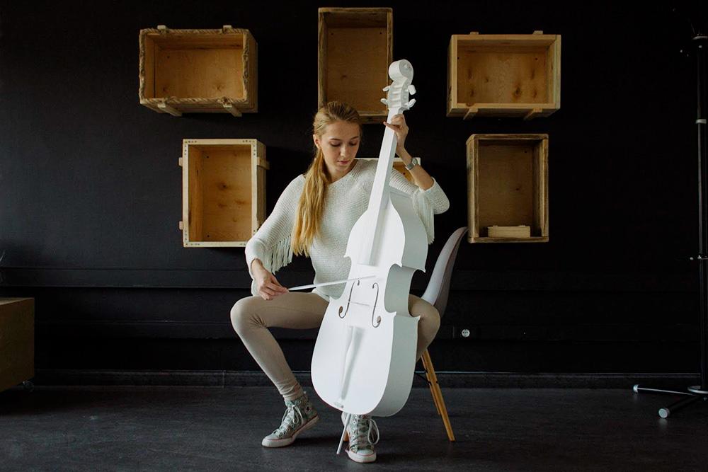 Александра позирует с бумажной виолончелью, которую заказали в подарок. Вместо струн — белые нити