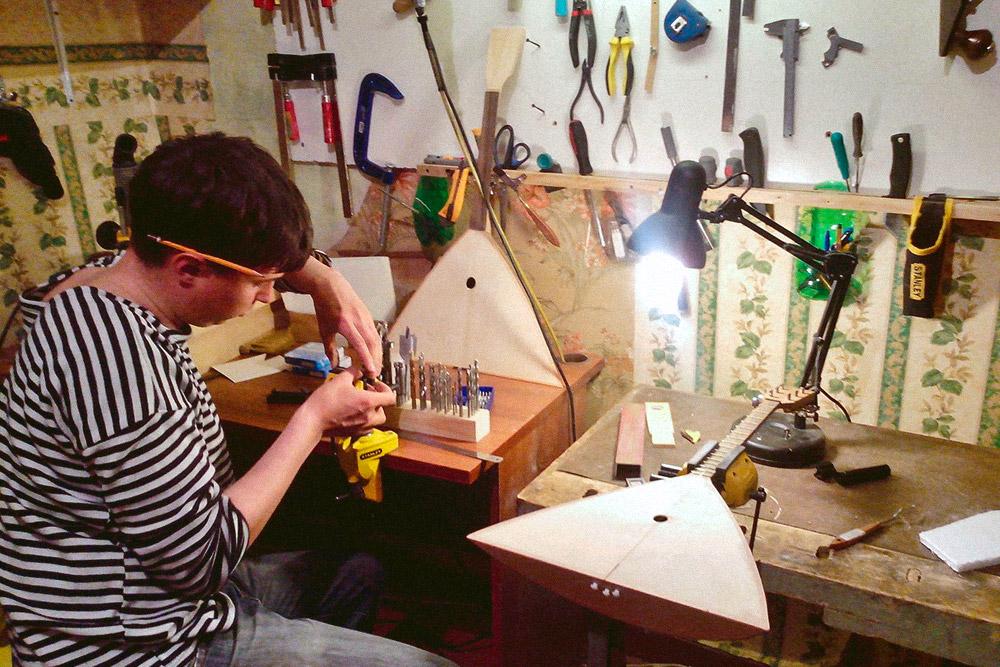 Александр сидит за верстаком в первой надомной мастерской мануфактуры. Он крепит на поворотные тиски прижимные губки. Они нужны длямягкого зажима заготовок, чтобы во время крепления и фиксации обрабатываемой детали дерево не травмировалось