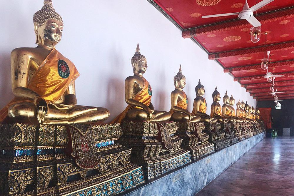 По периметру храма расставлены сотни разных статуй Будды, которые привезли из северных провинций Таиланда