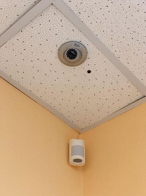 Сверху камера видеонаблюдения фирмы RVi. Черная точка справа от нее — микрофон длязаписи звука. Под камерой — датчик, который фиксирует движение. Если в нерабочее время преступник проникнет в помещение, датчик передаст сигнал тревоги на пульт охраны